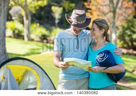 Happy hiker couple looking at map in forest