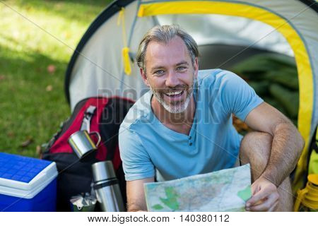 Portrait of happy hiker holding map in forest