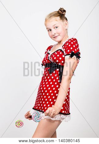 Portrait of happy beautiful young girl with sweet candys. pretty young woman dressed in a red dress with white polka dots holding two colorful lollipop.