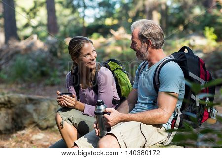 Hiker couple having coffee in forest