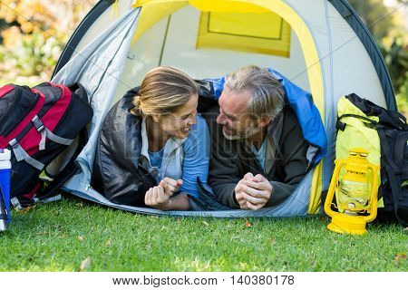 Happy hiker couple looking at each other in tent