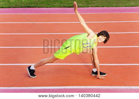 Portrait of teenage athlete in sportswear exercising outdoors on the stadium's track, top view