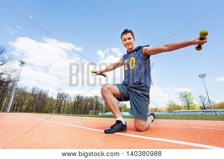 Picture of active teenage boy doing exercises with dumbbells standing on his knee on stadium
