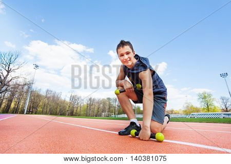 Teenage active boy picking up dumbbells, kneeling on track on the stadium in spring day