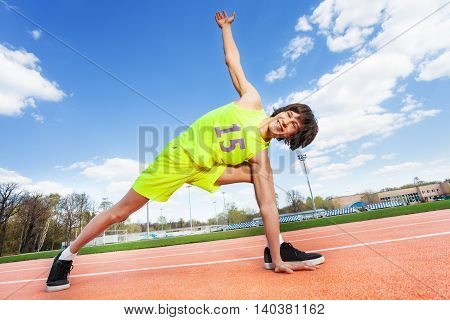Portrait of active teenage athlete in sportswear exercising outdoors on the stadium, bottom view