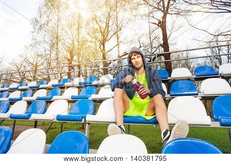 Teenage athlete having rest after working out, sitting at the tribune with the water bottle