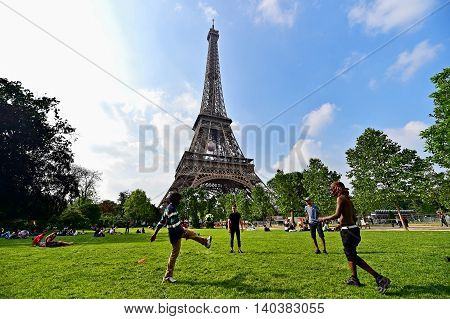 PARIS FRANCE - JUNE 8: People playing soccer in Champ de Mars park near the Eiffel Tower during the UEFA 2016 European Championship on June 8 2016 in Paris.