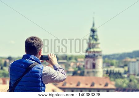 Young man making mobile camera photo of Cesky Krumlov landmark and architecture. Tourist in historical center. Male photographer travels around Europe Czech Republic. Vintage color tone.