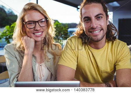 Portrait of happy young couple using digital tablet in cafeteria