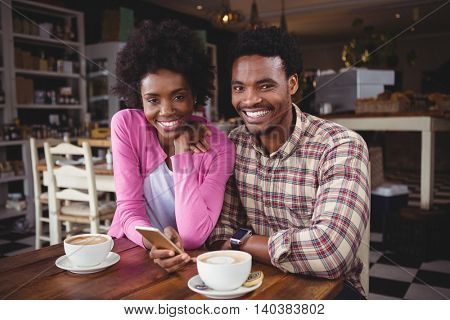 Portrait of happy young couple sitting at table using mobile phone in cafeteria
