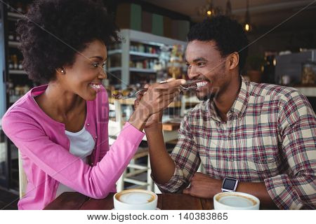 Romantic young couple feeding each other in cafeteria