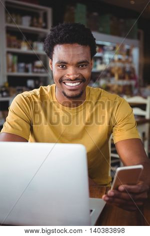 Portrait of young man text messaging on mobile phone while using laptop in cafeteria