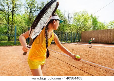 Female tennis player in yellow sportswear starting set, holding tennis ball and racket on the clay court