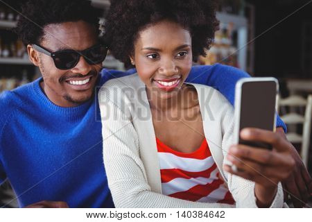 Smiling couple taking a selfie at cafe