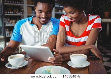 Smiling couple using digital tablet while having cup of coffee in cafe