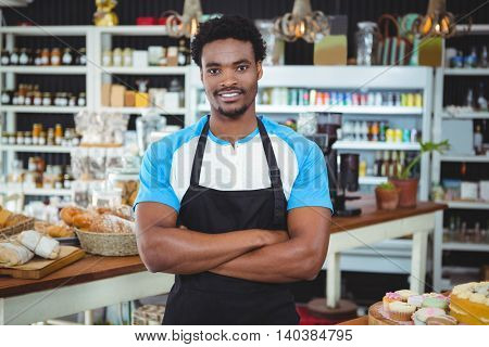 Portrait of smiling waiter standing with arms crossed in cafe