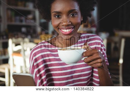 Smiling woman using mobile phone while having cup of coffee in cafe