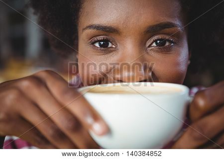 Portrait of woman drinking cup of coffee in cafe