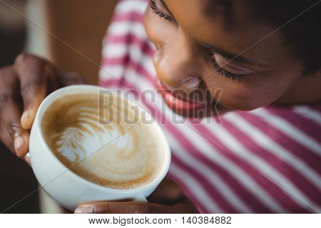 Close-up of woman drinking cup of coffee in cafe