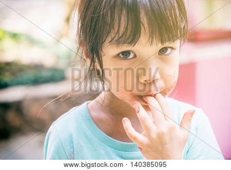 Hungry poor asian child licking her hand for the last test of her food.