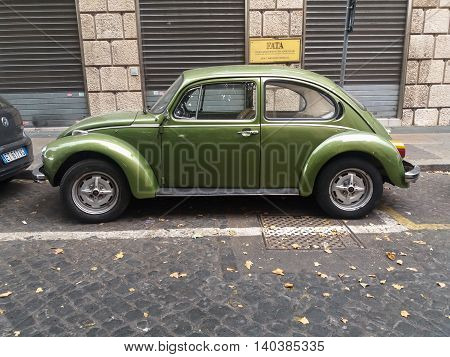 ROME ITALY - CIRCA JULY 2016: olive green Volkswagen Beetle car parked in a street of the city centre
