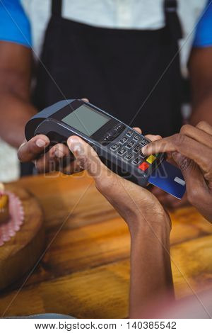 Customer paying by credit card in cafe