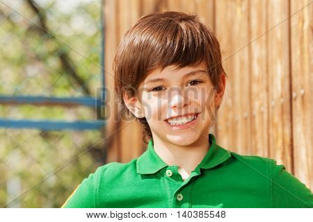 Close-up portrait of smiling ten years old boy in green polo shirt