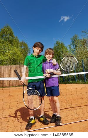 Full-length portrait of two tennis players, young boys, standing together next to the tennis net, holding tennis rackets