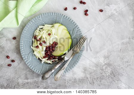 Healthy autumn or winter salad with apple, cabbage and pomegranate seeds. Top view. Space for text