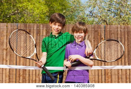Portrait of two happy friends, young boys, standing together next to the net after tennis match
