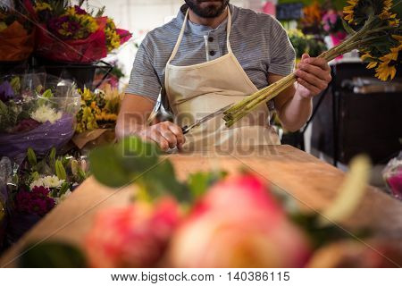 Male florist trimming flower stem at his flower shop