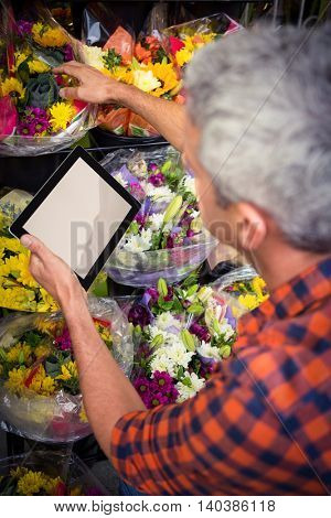 Male florist checking order on digital tablet at his flower shop