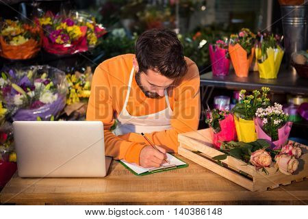 Male florist noting order in notepad at his flower shop