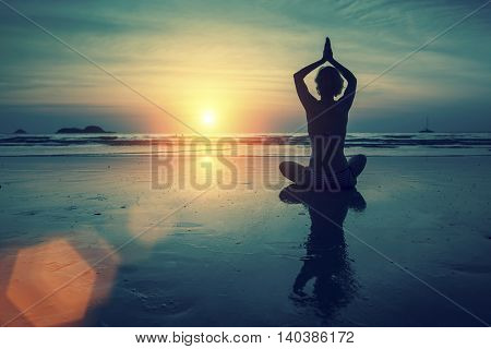 Silhouette of woman practicing yoga in Lotus position at sunset on the sea coast.