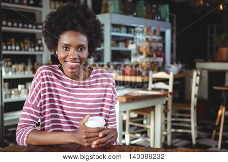 Portrait of smiling woman holding disposable coffee cup in cafe