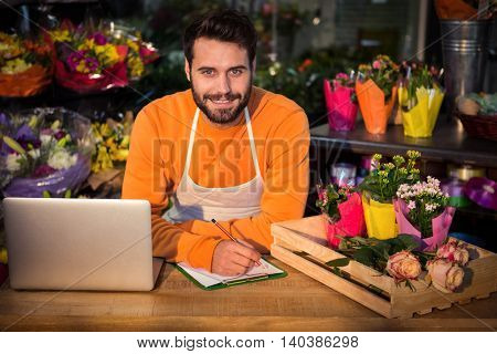 Portrait of male florist noting order in notepad at his flower shop