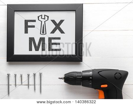 Fix me text on black frame with equipments. Fix me conceptual for broken heart person or depress person asking someone to fix the person. Power drill with screws