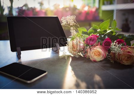 Flower bouquet with smartphone and digital tablet on the table at flower shop