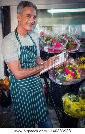 Portrait of male florist checking checklist at his flower shop