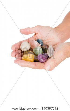 Cropped image of person holding colorful pebbles against white background