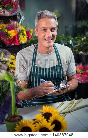 Portrait of happy male florist writing on clipboard at his flower shop