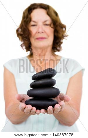 Mature woman holding pebbles against white background