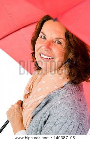 Portrait of happy mature woman holding red umbrella while standing against white background