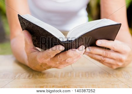 Midsection of woman reading bible at table