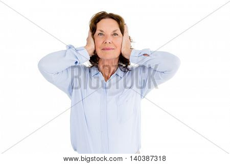 Portrait of smiling woman with hands covering ears against white background