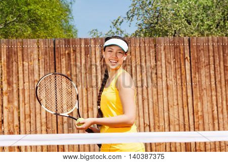 Portrait of happy young girl playing tennis outdoors in summer