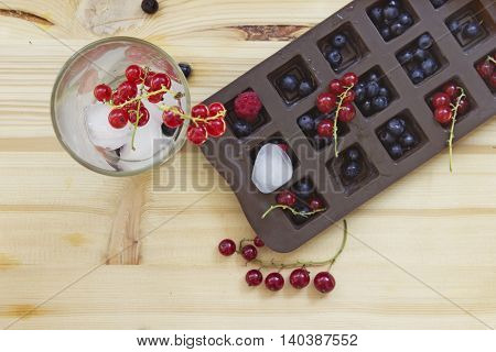 Fresh berries and drink in a glass with ice cubes. Blueberries and red currants on a wooden table background. Top view.