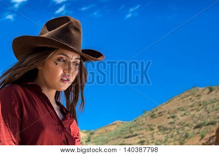 girl in a cowboy hat on a background of mountains