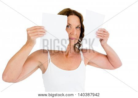 Portrait of mature woman holding torn papers against white background