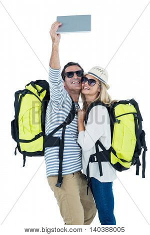 Happy couple taking selfie on digital tablet against white background